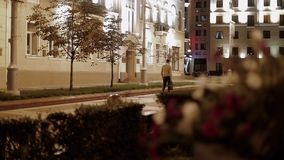 A businessman in a beige jacket with a bag in his hand walks through the night city. Beautiful street flowers in defocus. Back view. Slow motion stock video footage