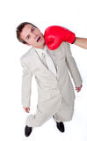 Businessman being hit with a boxing glove. Caucasian businessman being hit with a boxing glove isolated on a white background Stock Photo