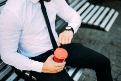 Close up Businessman On Bench With Coffee look at clock to be in time from pause at work Royalty Free Stock Images