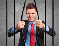 Businessman bending the bars of his prison. Angry strong businessman bending the bars of his prison trying to get out Royalty Free Stock Images
