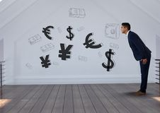 Businessman bending  in front of money on wall Stock Photo