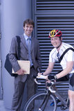Businessman by bicycle courier, smiling, portrait Royalty Free Stock Photography