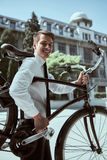 Businessman with bicycle. Handsome active businessman riding a bicycle on the way to job stock photos