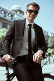 Businessman with bicycle. Handsome active businessman riding a bicycle on the way to job stock image