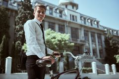 Businessman with bicycle. Handsome active businessman riding a bicycle on the way to job royalty free stock images
