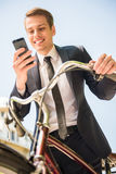 Businessman with bicycle. Handsome active businessman riding a bicycle on the way to job stock images
