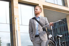 Businessman with bicycle looking away while standing outside office building Stock Photo