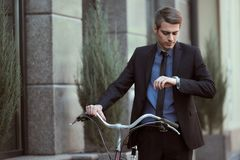 Businessman with bicycle. Portrait of young businessman riding bicycle to work on urban street royalty free stock image