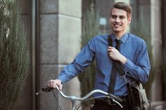 Businessman with bicycle. Portrait of young businessman riding bicycle to work on urban street stock image