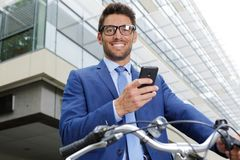 Businessman with bicycle using smartphone stock image