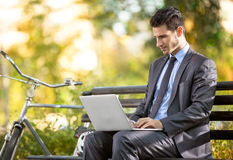 Businessman with bicycle working on laptop Royalty Free Stock Photography