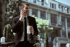 Businessman with bicycle. Young cheerful businessman riding a bicycle and using phone go to work stock photos