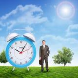 Businessman with big alarm clock Stock Images