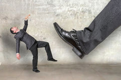 Businessman big foot kicking small businessman Royalty Free Stock Image