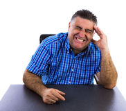 Businessman with big headache. Sitting at a desk in his office holding his head in his hand Royalty Free Stock Photos