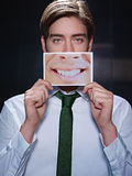 Businessman with big mouth smiling at camera. Young business man holding photo of toothy smile on black background. Vertical shape, front view, waist up Royalty Free Stock Image