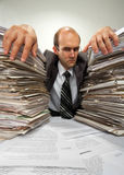 Businessman with big piles of paperwork stock images