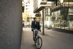 Businessman on a bike. Business man driving bike on street. royalty free stock photography
