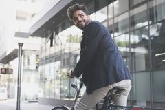 Smiling and happy businessman on a bike. royalty free stock images