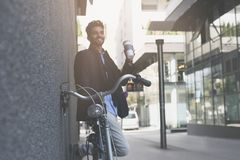 Businessman with bike using iPod on street. Space for copy Stock Photos