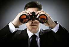 Businessman with binoculars. Over gray background Royalty Free Stock Image