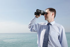 Businessman with binoculars Stock Image