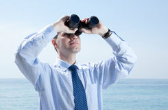 Businessman with binoculars against blue sky Stock Photos