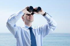Businessman with binoculars against blue sky Stock Photos