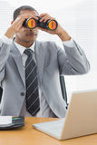Businessman with binoculars in front of laptop at office Stock Image