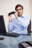 Businessman with binoculars in his office Stock Image