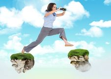 Businessman with binoculars jumping between floating rock platforms in sky Stock Photo