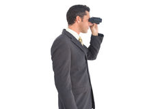 Businessman with binoculars looking on the right Royalty Free Stock Photography