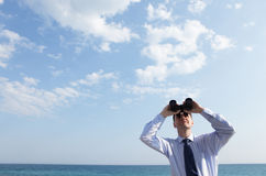 Businessman with binoculars. Looking upward against a sea and skyscape Stock Photos