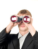 Businessman with binoculars searching. For something isolated over white Stock Photo