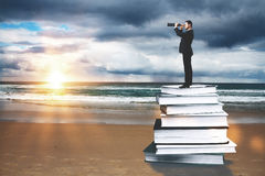 Businessman with binoculars. Standing on abstract book pile at the beach with sunset. Education and research concept royalty free stock photos