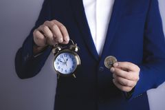Businessman with bitcoin and clock stock images