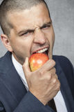 Businessman biting the apple Royalty Free Stock Image