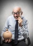 Businessman biting a coin Stock Photos