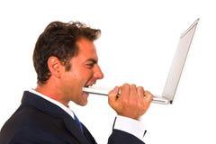 Businessman biting a computer Stock Photo