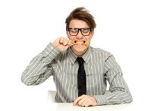 Businessman biting pen Royalty Free Stock Photography