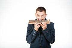 Businessman biting wooden timber Royalty Free Stock Photos