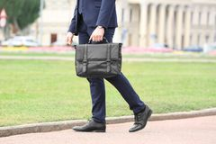 Businessman with black briefcase in hand. Outdoors stock photos