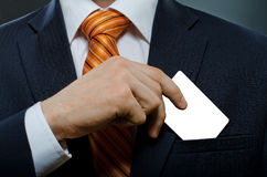 Businessman. In black costume and orange necktie put or take out credit card in pocket Royalty Free Stock Photo