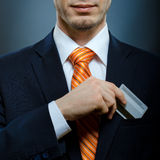 Businessman. In black costume and orange necktie put or take out credit card in pocket Royalty Free Stock Images