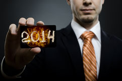 Businessman. In black costume and orange necktie reach out on camera and show credit card with date 2014, close up Royalty Free Stock Images