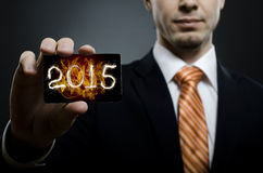 Businessman. In black costume and orange necktie reach out on camera and show credit card with date 2015, close up Stock Photos