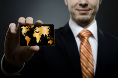 Businessman. In black costume and orange necktie reach out on camera and show credit card or visiting card, close up Royalty Free Stock Image