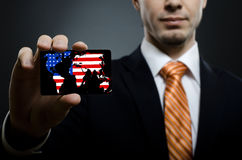 Businessman. In black costume and orange necktie reach out on camera and show credit card or visiting card, close up Stock Image