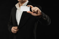 The businessman in black costume showing credit card or visiting card Royalty Free Stock Image