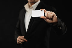 The businessman in black costume showing credit card or visiting card Stock Photos
